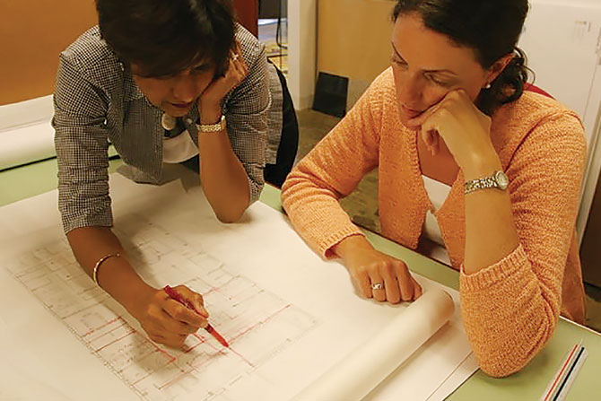 two-women-discussing-blueprints
